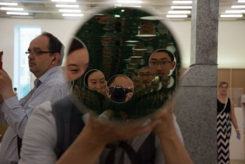 people looking into a mirror with their camera