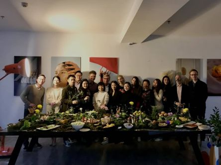 Group photo with a table of food in front
