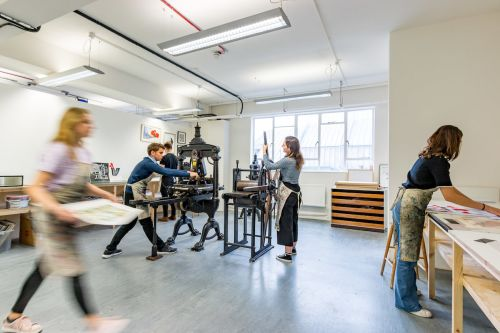 Students using a printing press  inside Central Saint Martins' Archway campus