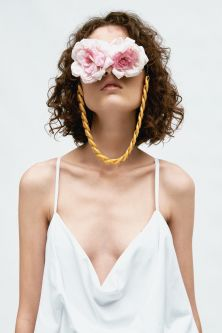 close up of model in white garment, wearing pink rose petal glasses that completely cover the eyes, with gold chain