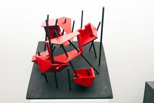 A wooden, sculptural object, features red geometric shapes impaled on black sticks.