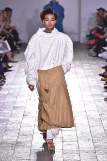 A model walking down a catwalk wearing a camel coloured skirt and a white top which has an exaggerated collar