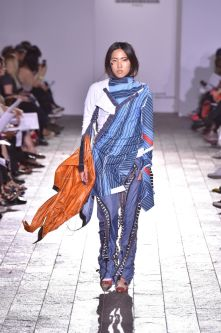 A model walking down a catwalk in a garment made of varying shades of blue and some red detailing.