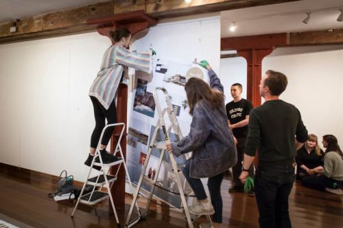 Students up a ladder installing an exhibition
