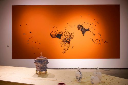 A large orange canvas which is covered in black dots which form the shape of a map