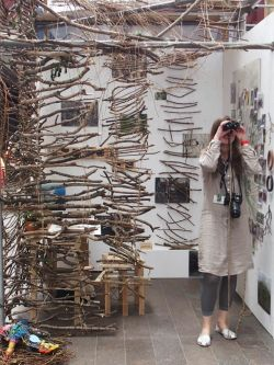 A woman looking through binoculars inside a room filled with lots of wooden sticks