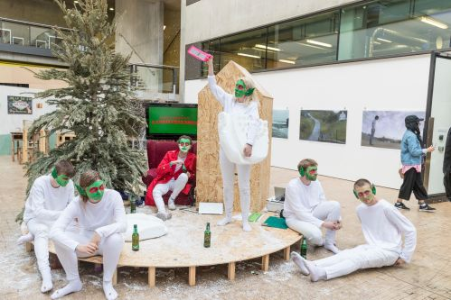 A group of people dressed as elves surrounded by fake snow
