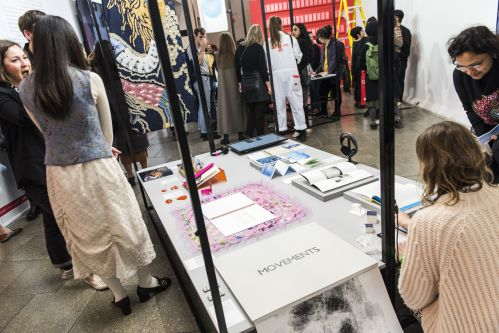 image of student work displayed on a table during exhibition launch night with people standing around