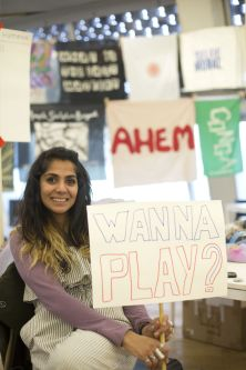 Woman holding sign saying 'wanna play?'