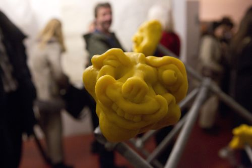 Detail of a sculpture with distored yellow face