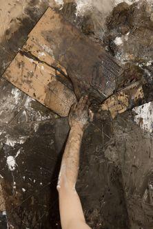 Hand among dirt on piece of cardboard