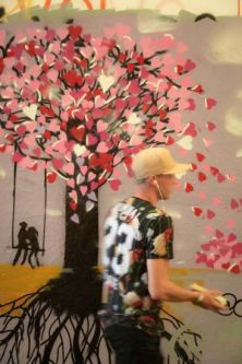 blurred figure in front of tree artwork on wall