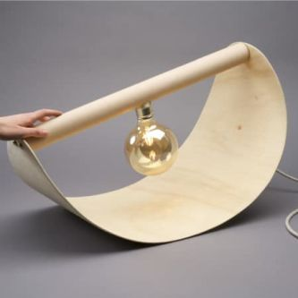 a lightbulb attached to a curved piece of wood