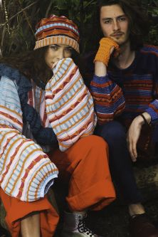 Female model wearing blue and orange knitted hat and jumper with red trousers next to male model wearing a red and blue knitted jumper with orange gloves