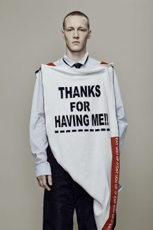 Male model wearing a knitted vest that says thanks for having me in black capital letters on a white background
