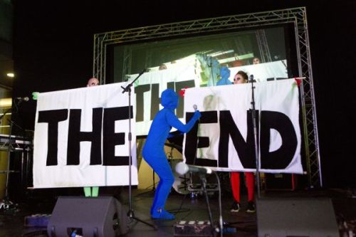 Photograph of two people on a stage holding up signs that say The and End with a third person bent over between them, dressed in a blue morph suit, with a microphone in their hand