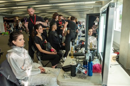 A row of female models getting their makeup done backstage