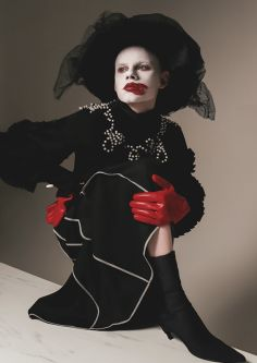 Model wearing a black hat and coat and red gloves with pale white makeup and smudged red lips