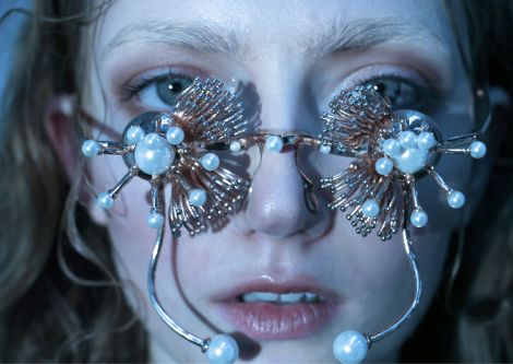 Female model closeup wearing gold flower shaped glasses with pearls