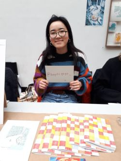 student at holiday market holdin gup a card with instagram handle written onto it