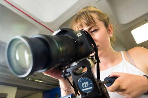Student looking at a camera with large lens.