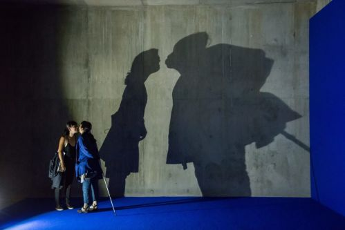 people kissing with their shadow on the wall behind them