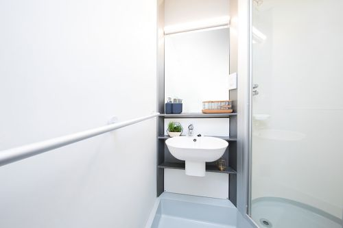 Ensuite bathroom with large mirror, sink, shelf, towel holder, shelf, toilet and shower enclosed with a glass door