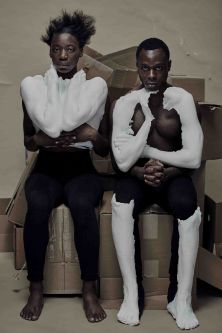 Two models sit on cardboard boxes while wearing plaster-cast items.