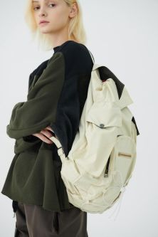 Model with blonde hair wearing a cream backpack