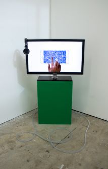 a tv screen placed on top of a green plinth
