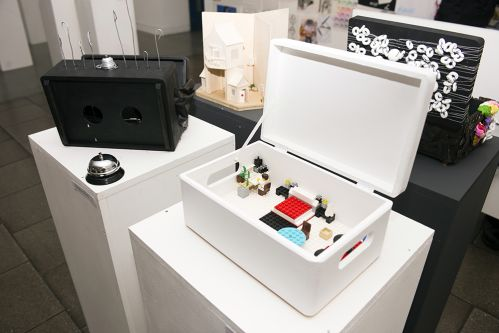 Two different boxes atop white plinths. The closest is white and is open, revealing a domestic scene made out of lego blocks and figures. The other is black and has two circles cut out of it with bent silver wires protruding from it's top. Alongside the black box is a silver desk bell.