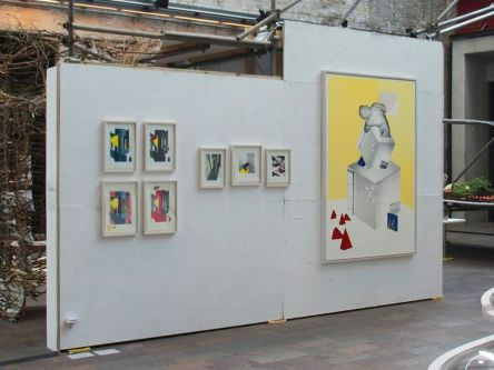 Framed abstract drawings hung on a white wall