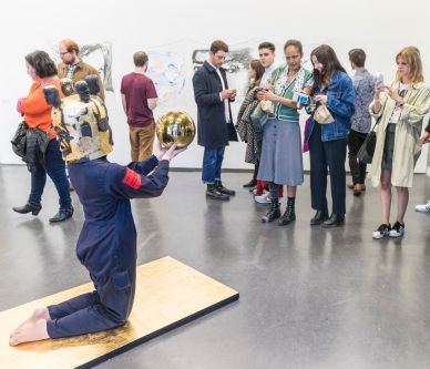 A person kneeling on the floor wearing an abstract costume, people are observing the performance