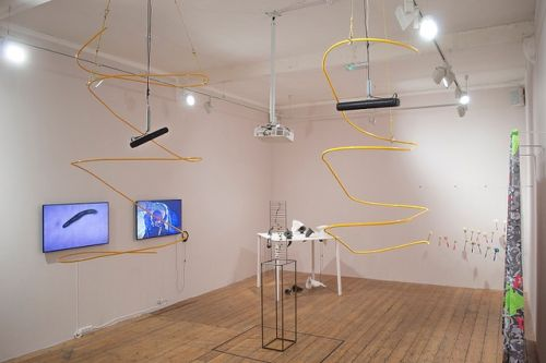 An exhibtion in a gallery with screens and yellow metal sculptures