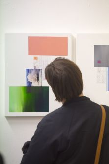 Person looking at green and pink painting