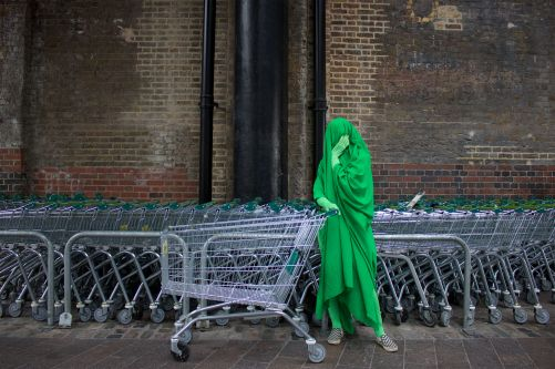 A person dressed entirely in bright green stands next to a row of shopping trolleys