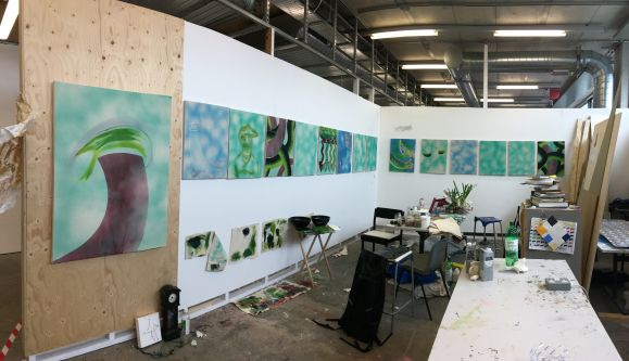 Nineteen paintings arranged in studio