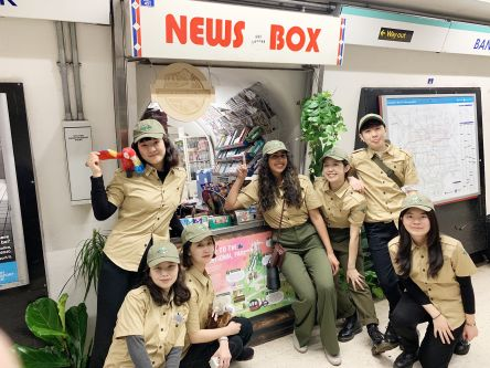 Students dressed as park rangers stand outside a news kiosk at bank station