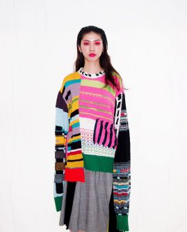 Female model wearing a patchwork multicoloured jumper with a tartan skirt