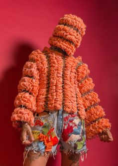 Male model with face covered by peach knitted fabric wearing a peach knitted jumper in front of a pink background
