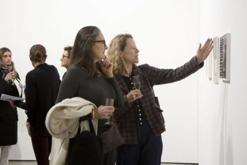 Two women looking at artwork hung on a wall, one of them gesturing towards the work in mid discussion