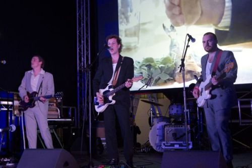 Photograph of three men on stage in suits, performing with guitars