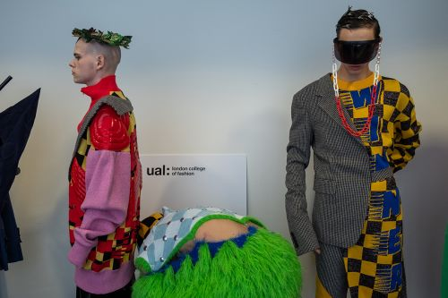 Male models waiting backstage, the model on the left wears a pink and red jacket and the model on the right wears a grey and yellow checked coat