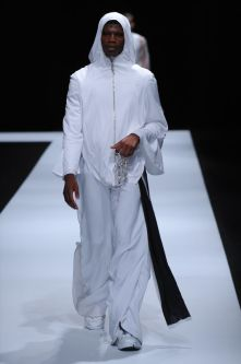 Male model wearing all white clothing with white hood.