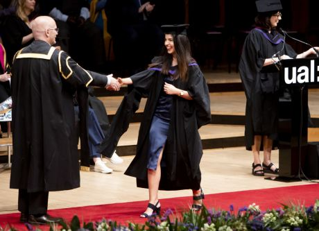 Graduate receiving her award on stage and shaking hands.