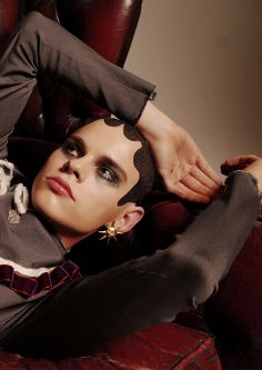 Model resting arm on head with short hair and heavy eye makeup