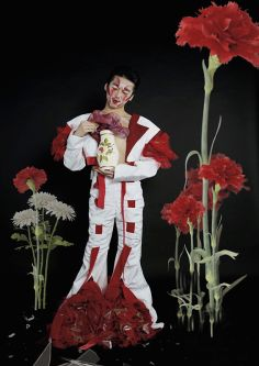 Male model in a white suit with red inserts with large poppies in the background