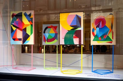 Four colourful and geometric paintings on colourful metal stands, being displayed in a shop window