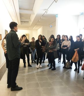 Image of curator talking to students in gallery space