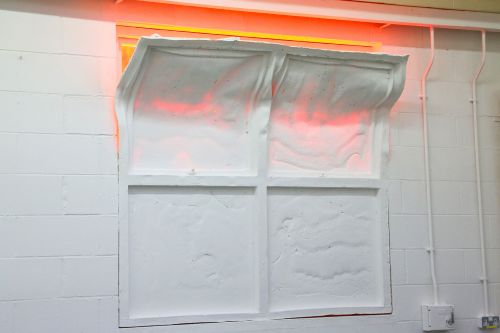 Sculptural intervention creating a red glow beyond the window by Rachel Wrigley.
